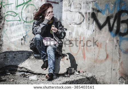 young girl in old dirty ragged clothes, no shoes sitting on a rock, and debris scattered around holding a cigarette and a match. Homeless girl. A homeless teenager. - stock photo