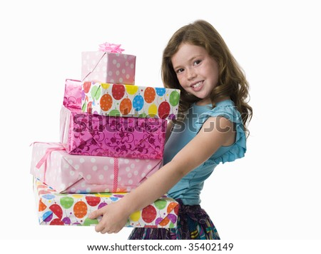 Young girl in party clothes holding large pile of presents