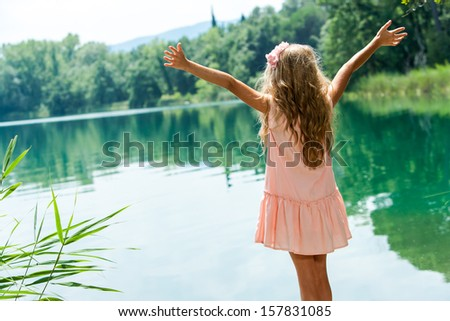 Young girl in pink dress standing with open arms at lakeside. - stock photo