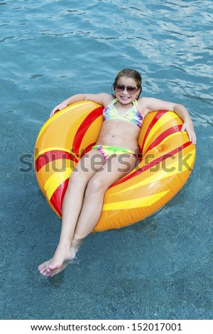 Young girl in pool on float - stock photo