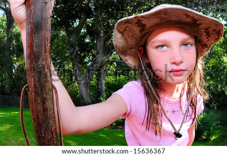 Young girl in pretty outdoors with walking stick for hike - stock photo