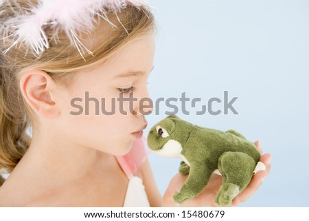 Young girl in princess costume kissing plush frog - stock photo