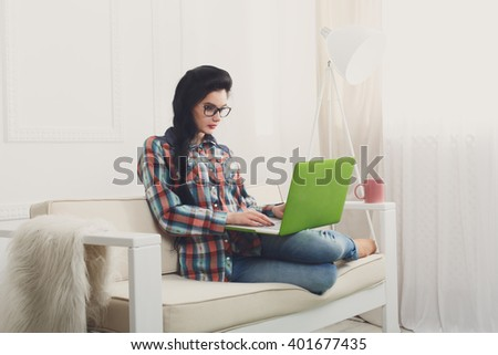 Young girl in protective computer glasses on a white sofa with laptop. Hipster freelancer woman works at home. Home office, freelance. Brunette with laptop in modern interior at white couch. Soft tone - stock photo