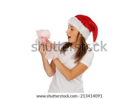 Young girl in red Santa Hat looking at a small plush pink teddy bear Christmas gift that she is holding in her hands with her mouth open in surprise, isolated on white - stock photo