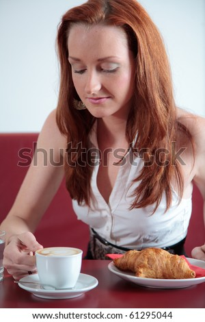 Young girl in restaurant in having coffee and croissant - stock photo