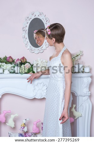 Young girl in retro style wedding dress is standing in front of a mirror - stock photo