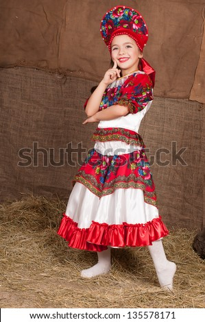 young girl in Russian national costume dancing to the music - stock photo