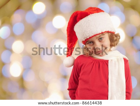 young girl in santa`s hat holding small christmas gift on shining background