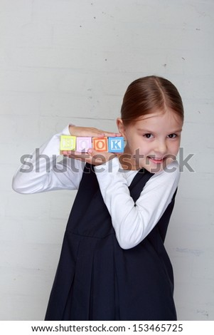 Young girl in school uniform playing with letter cubes and composes words - stock photo
