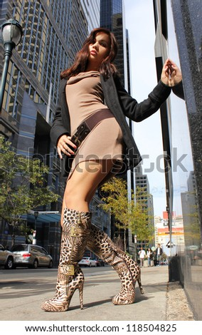 young girl in sexy boots posing in a city