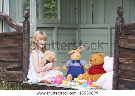 Young girl in shed playing tea and smiling - stock photo