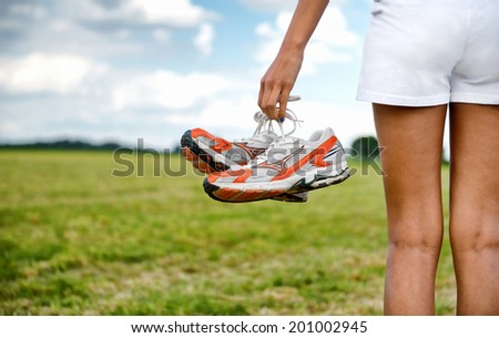 Young girl in shorts holding her sneakers in her hand as she stands looking out over a rural field, close up view of the shoes from behind - stock photo