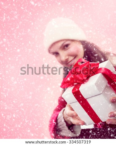 Young girl in snow gives a christmas gift with red bow and ribbon. - stock photo