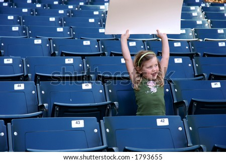 young girl in stadium seats with blank white sign - stock photo