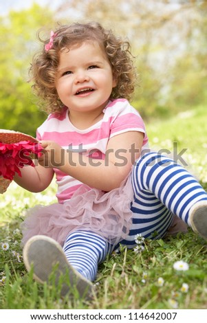 Young Girl In Summer Dress Sitting In Field Wearing Straw Hat