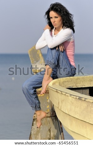 Young girl in summer time by the sea while resting on an old yellow fishing boat. Location: Poland Baltic Sea. - stock photo