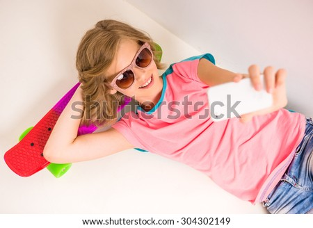 Young girl in sunglasses taking selfie while lying on skateboard against white background. - stock photo