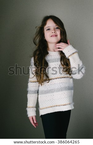 Young girl in sweater posing in studio