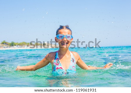 Young girl in swimming goggles playing in the wave with spray - stock photo