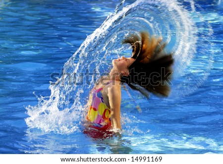 Young girl in swimming pool flipping wet hair