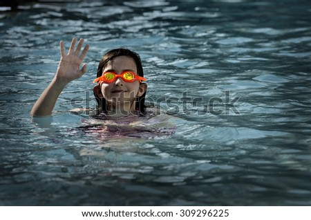 Young girl in swimming pool with wet hair bright orange goggles - stock photo