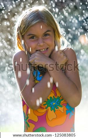 Young girl in swimsuit in sprinkler - stock photo