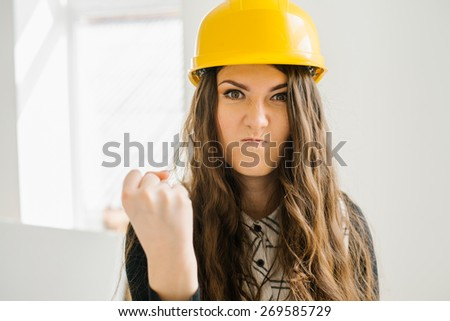 young girl in the construction helmet angry - stock photo