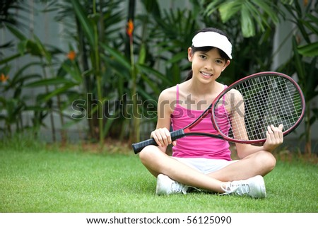 Young girl in the garden with tennis racket