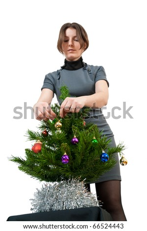 young girl in the hat of Santa Claus dresses up Christmas tree - stock photo