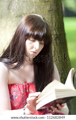Young Girl in the Park against a Tree Reading
