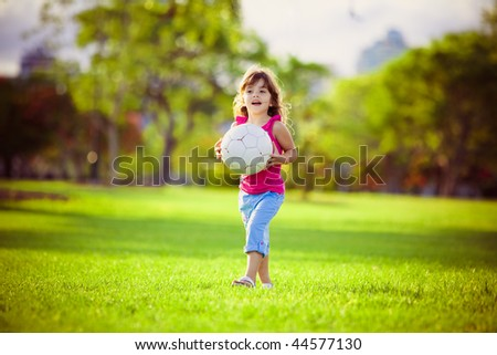 Young girl in the park holding large white ball - stock photo