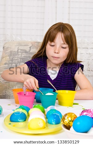 Young girl in the process of coloring Easter Eggs - Step four, the egg nearly submerged into the cup of dye