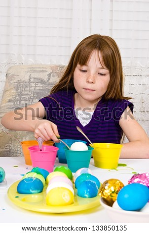 Young girl in the process of coloring Easter Eggs - Step three, lowering the egg partially into the cup of dye