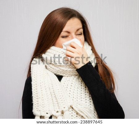 young girl in the scarf blowing her nose