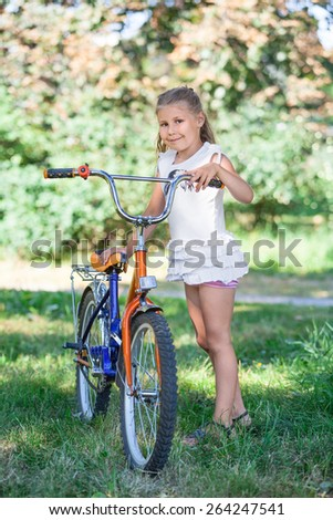 Young girl in the summer park on the grass next to bicycle - stock photo