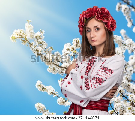 Young girl in the Ukrainian national suit against a blooming garden and blue sky with sun rays