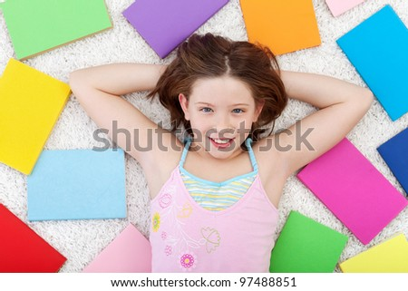 Young girl in the world books - on the floor smiling - stock photo