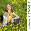 Young girl in the yellow flowers field. Outdoor shot. - stock photo