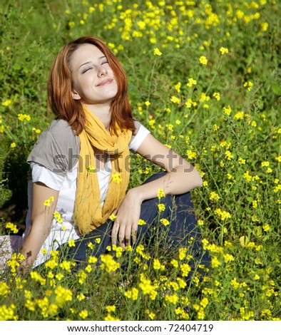 Young girl in the yellow flowers field. Outdoor shot.