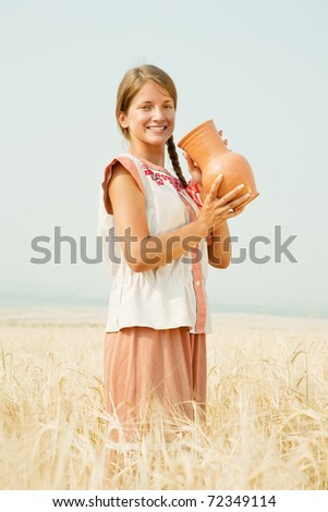 Young girl  in traditional clothes   with jug at cereals field in summer - stock photo