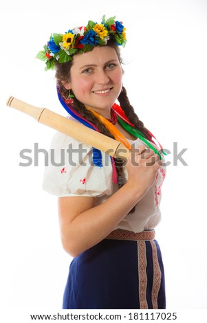 Young girl in Ukrainian national costume and  a wreath with ribbons rolling pin in her hand on his shoulder