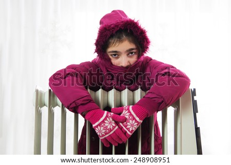 Young Girl in Warm Winter Jacket with Hood Near a Heater. - stock photo