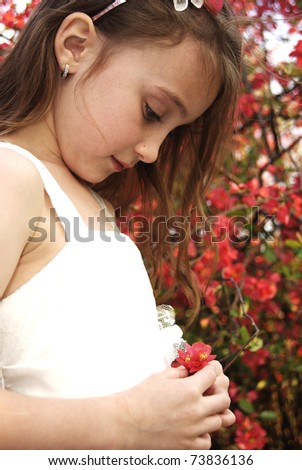 Young girl in white dress at the park with flowers - stock photo