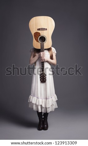 young girl in white dress holding a guitar in front of her head - stock photo