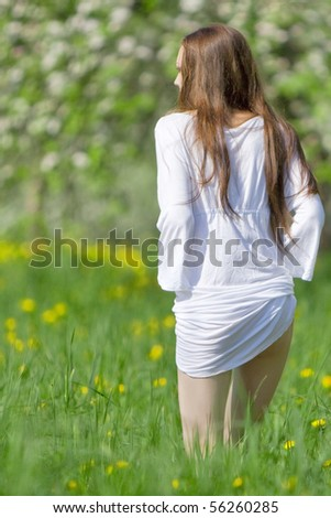 Young girl in white dress is on the meadow