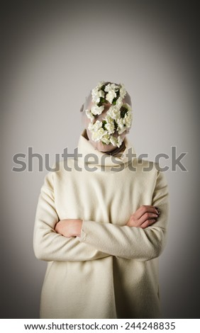Young girl in white wearing a floral mask having crossed her arms. - stock photo