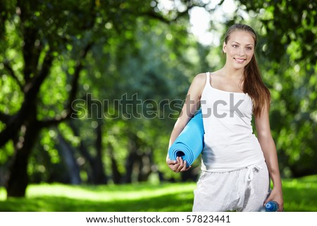 Young girl in white with a bottle of water and gymnastic mat - stock photo