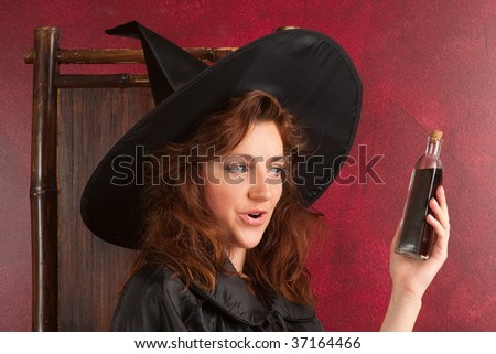 Young girl in witch hat and cape  holding vial with potion - stock photo
