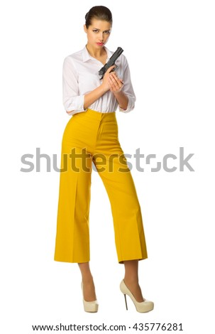 Young girl in yellow pants with gun isolated - stock photo