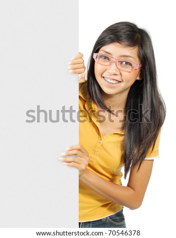 young girl in yellow shirt holding a big white card - stock photo